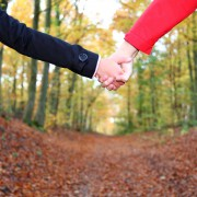 Young couple holding hands in during a walk in the autumn forest. Closeup.