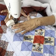 A woman machine quilting/sewing three layers to create a grid pattern on a patriotic quilt.